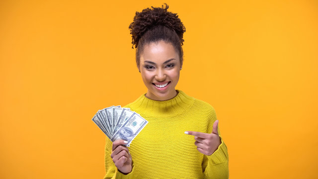Smiling young lady pointing at dollar banknotes in hand, bank credit, earnings