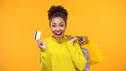 Adorable Afro-American lady holding credit card and purchase bags, shopaholic