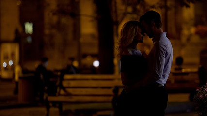 Romantic couple hugging and enjoying city park date in the evening, love