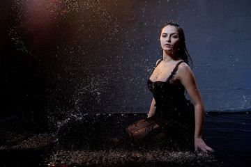 Beautiful sexy girl in black and water spray in the Studio on a dark background with orange back light