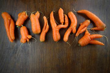 Raritäten: Ungenormte Bio Möhren mit Händen und Beinen auf Holznen aus dem Garten