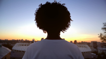 Afro-american curly haired woman enjoying sunset on roof, meditation, back view