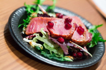 Raw tuna slices with frisee and pomegranate grains