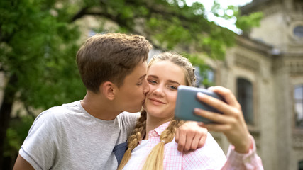 Couple of teens making selfie, boy kissing girl, photo for personal blog, love