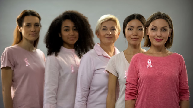 Group of women wearing pink clothes and ribbons, fighting against breast cancer