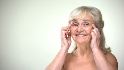 Attractive old lady doing facial exercises, anti-aging facebuilding for eyes