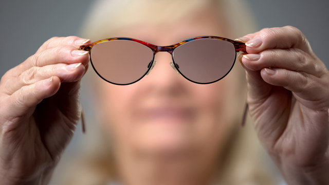 Old woman holding trendy glasses, concept of vision problems, blurred background