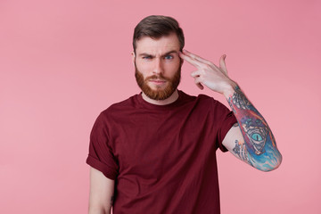 Photo of young bearded inked man isolated over pink background, shooting at his head with hand gun, showing suicide gesture.