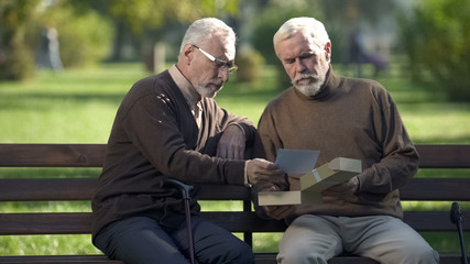 Two senior brothers looking at photo and remembering relatives, memories