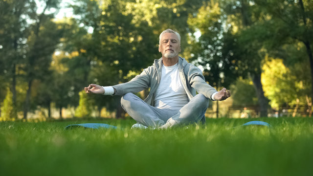 Healthy senior man meditating in park, sitting lotus pose on yoga mat, zen
