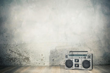 Retro outdated portable stereo boombox radio cassette recorder from 80s front concrete wall background with shadow. Vintage old style filtered photo