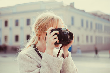 Beauty woman using vintage camera, make photo in the street, outdoor hipster portrait