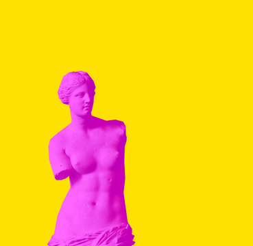 The Venus de Milo is an ancient Greek statue created between 130 and 100 BC. Creative magazine style concept of red neon Aphrodite woman on yellow background.