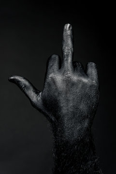 full black hand showing middle finger on black background