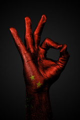 A hand with the painted flag of china shows an OK sign on a dark background.