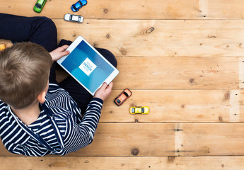 Young Tablet User Sitting on a Wooden Floor Mockup