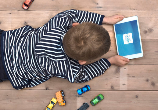 Young Tablet User laying on a Wooden Floor Mockup