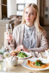 Portrait of a beautiful young elegant blonde woman in the cafe with a glass of champagne.