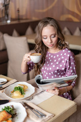 Nice woman eat breakfast in cafe. Reading a magazine. Portrait of young charming female drinking coffee and eat eggs Benedict in modern coffee shop.