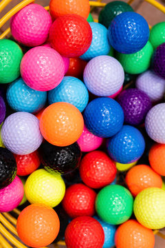 Colorful golf balls in wire bucket for putt-putt or driving range