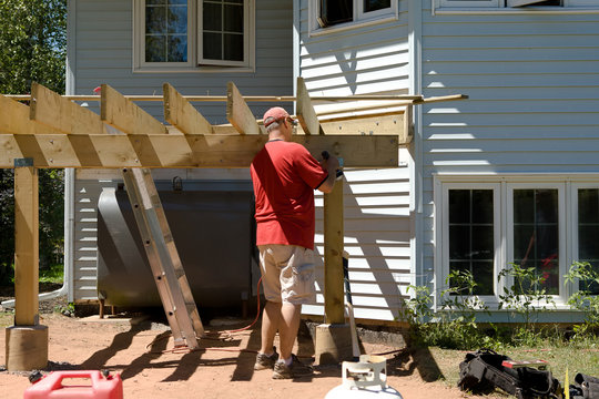 A man is building a back deck on his own in summer