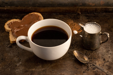 three-quarter view of black coffee with creamer and toast with chocolate in rustic dark setting