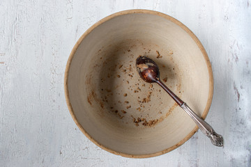 empty country crock bowl with wooden spoon and leftover crumbs flat lay
