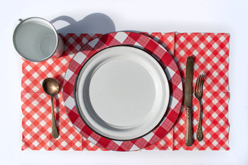 flat lay picnic table place setting of plate, cup, silverware, and checkered tablecloth