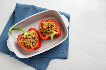 stuffed red peppers in a baking dish on a blue napkin and a white table, copy space, high angle view from above
