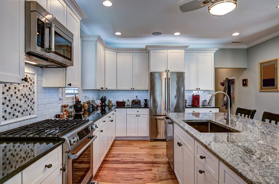 High-end luxury kitchen with granite countertops and white cabinets.