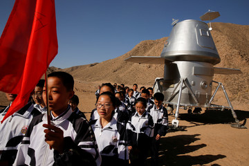 Students leave a mock space capsule after a lesson at the C-Space Project Mars simulation base in the Gobi Desert outside Jinchang