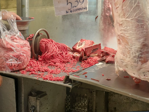 a butcher grinds miced meat at athens central market