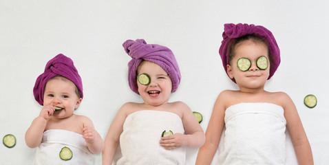 Adorable sisters wearing bath turbans, white towels and  cucumber face masks