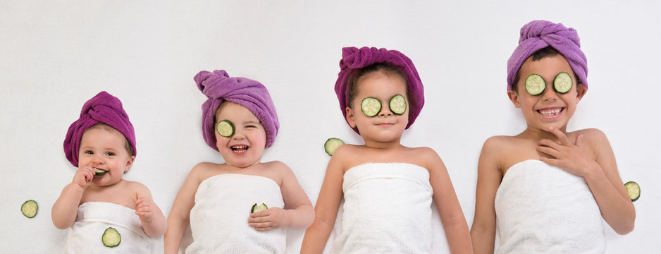 Funny kids and baby in bath turbans and towels getting beauty treatments
