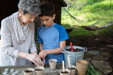 A boy and his grandmother planting seeds in the garden