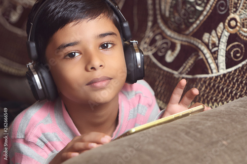 Indian young boy listen music with headphone