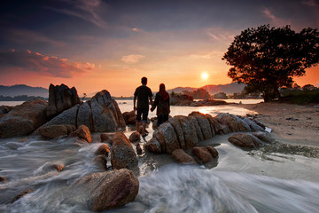 Wall Mural - Sweet couple looking at beautiful sunset at the beach in Pangkor island, Malaysia