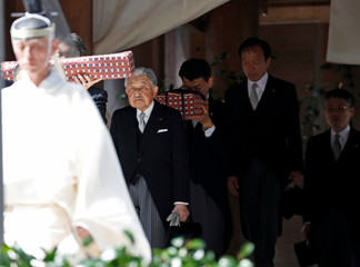 Japan's Emperor Akihito is led by a Shinto priest as he leaves the main sanctuary during his visits at Inner shrine of the Ise Jingu shrine in Ise