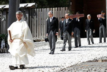 Japan's Emperor Akihito, flanked by Imperial Household Agency officials carrying two of the so-called Three Sacred Treasures of Japan, leaves the main sanctuary as he visits the Inner shrine of the Ise Jingu shrine in Ise, Japan