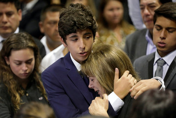 Federico Danton, son of Peru's former President Alan Garcia, hugs his mother Roxanne Cheesman during a wake for Garcia after he fatally shot himself on Wednesday, in Lima
