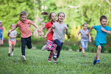 A group of happy children of boys and girls run in the Park on the grass on a Sunny summer day . The concept of ethnic friendship, peace, kindness, childhood. Fotoväggar