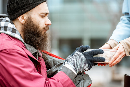 Woman helping homeless beggar giving some food outdoors, close-up view. Concept of helping poor people