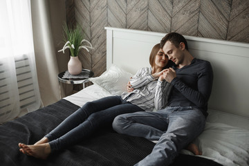 girl relaxes with her boyfriend on the bed