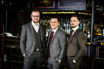Three successful stylish businessmen in a pub. Three business partners in classic suits in a nightclub