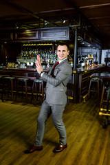 charismatic businessman in a smart suit against the backdrop of a pub