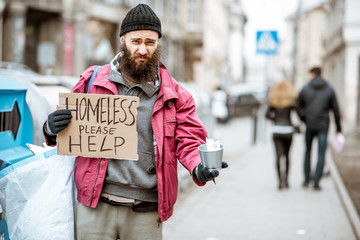 Portrait of a depressed homeless beggar with cardboard begging some money on the street in the city
