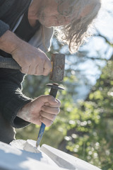 Closeup of a senior artist using mallet and a chisel to carve in stone