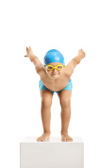 Little boy swimmer with a cap and googles preparing to jump and swim