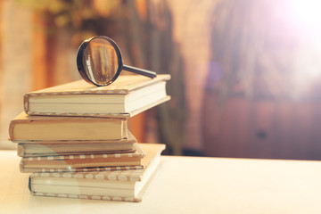 book and magnifying glass on wooden background