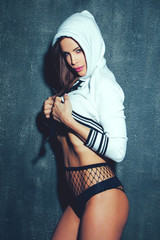 Sexy brunette woman in short pullover with hoodies holding tits at night